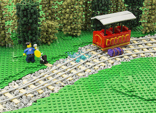 lego train with two tracks and a lego man holding a lever